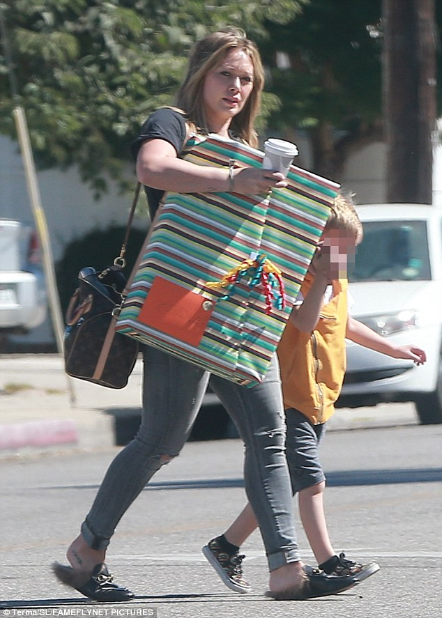 On-the-go: Hilary Duff was spotted with her hands full while out and about with her son Luca in Beverly Hills on Sunday
