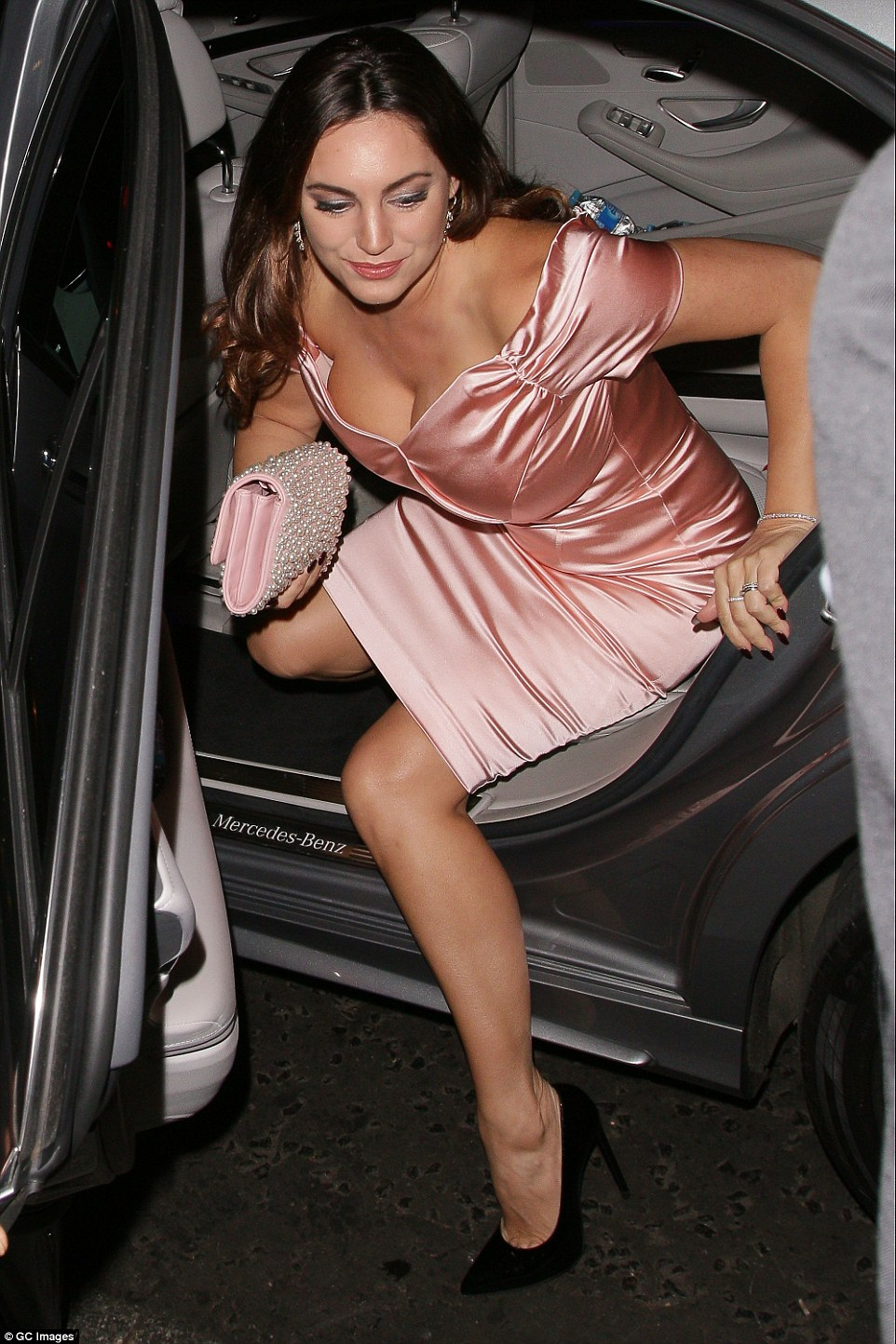 Pretty in pink: Kelly gracefully departed her car showing off her figure as she climbed out