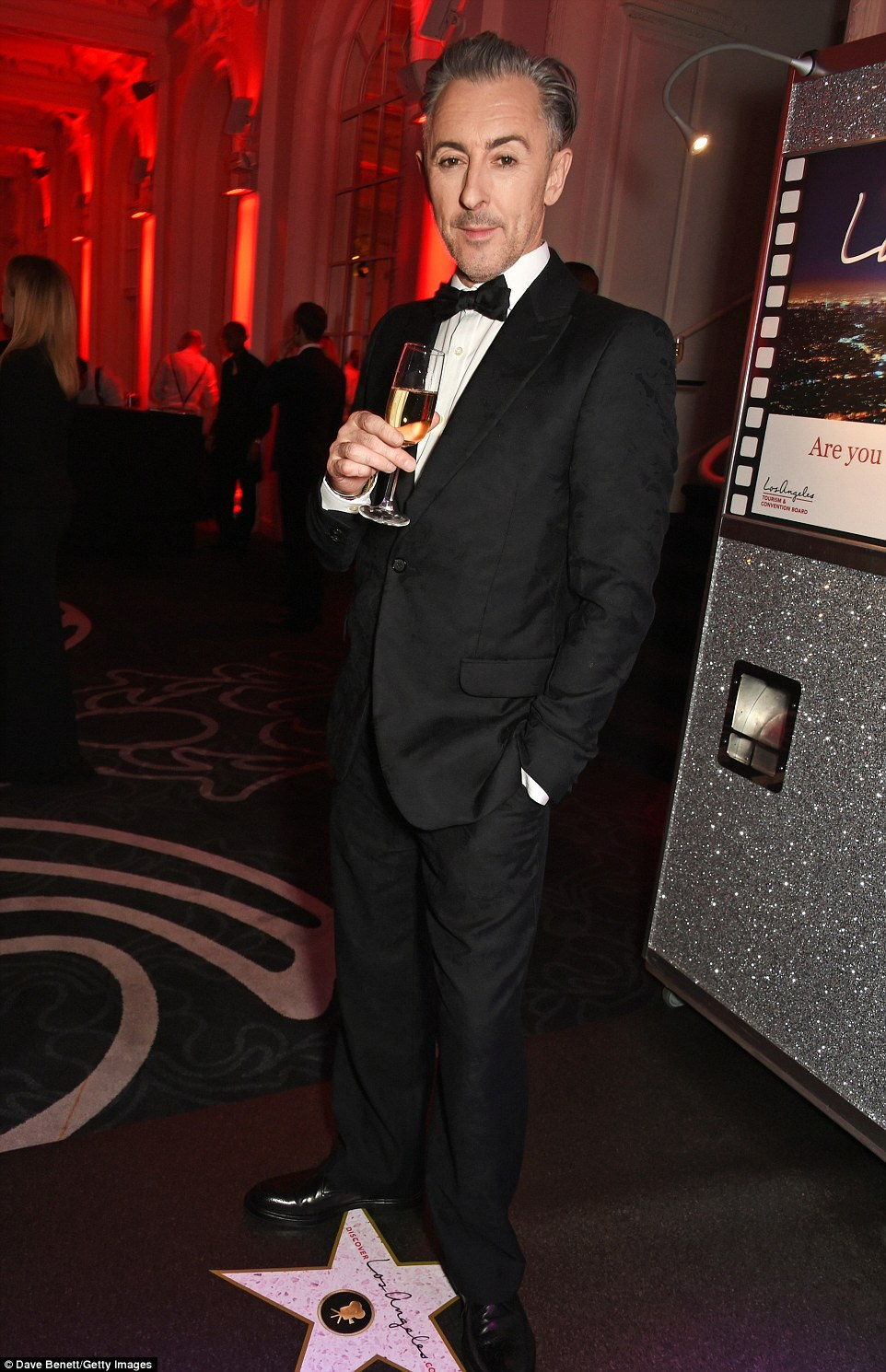 Slick: Leading the male arrivals was the show's debonair host Alan Cumming, who looked sharp in a tuxedo while showing off his salt and pepper hair, which was slicked into a chic hairstyle
