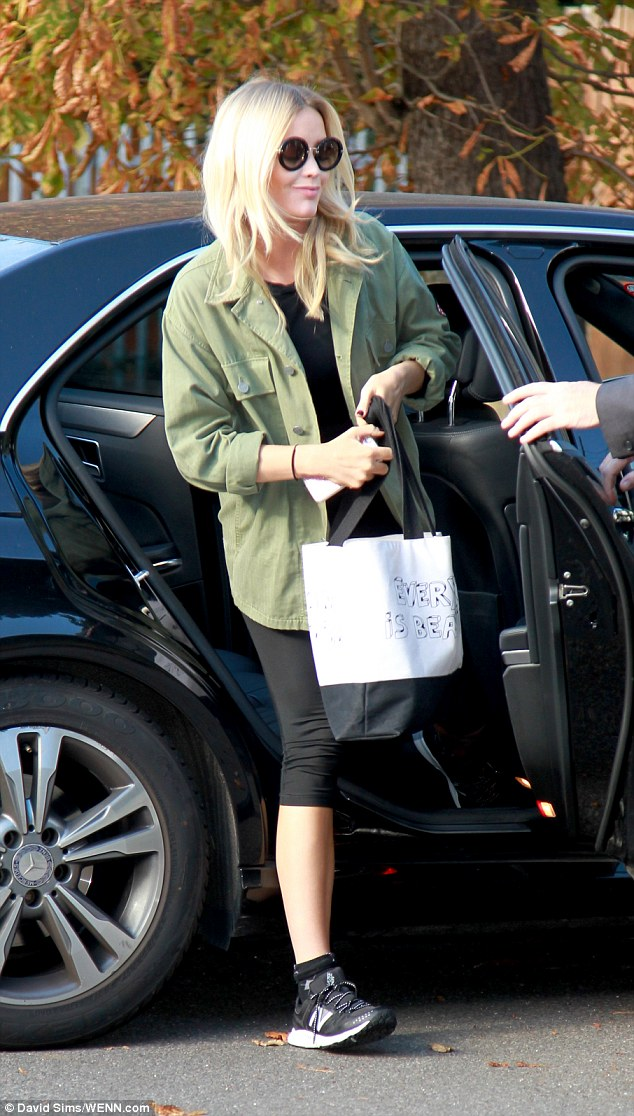 Dressed down: The blonde bombshell was rocking a pair of coordinating trainers and a slogan emblazoned handbag