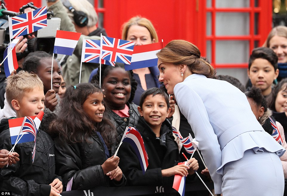 Mother-of-two Kate looks animated as she chats you young well wishers on her visit to The Hague - her first official overseas trip without Prince William