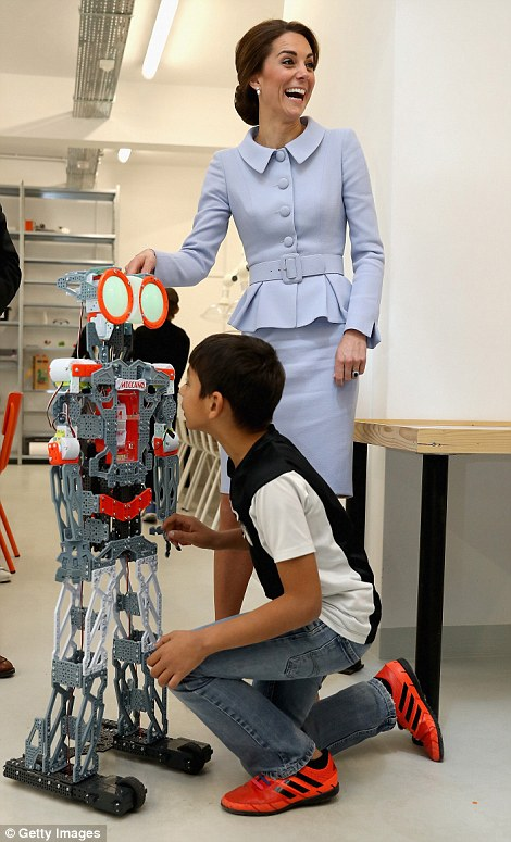 Kate collapses into giggles as she is introduced to a robot by a local youngster at Bouwkeet for teenagers