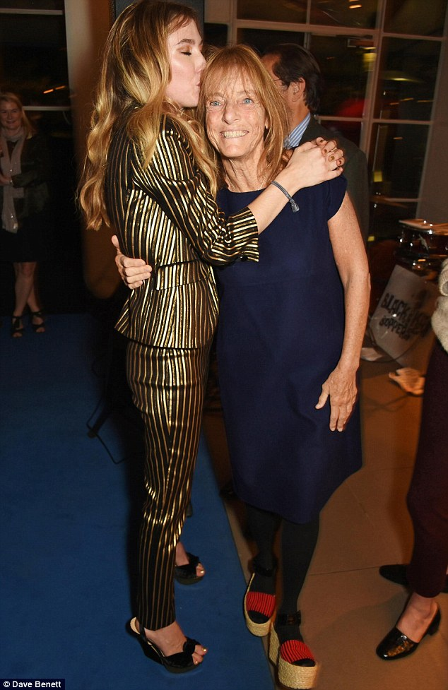 Leggy lady:The matching trousers perfectly hugged her slender legs, before they met a chic matching pair of black and gold velvet wedges at the bottom