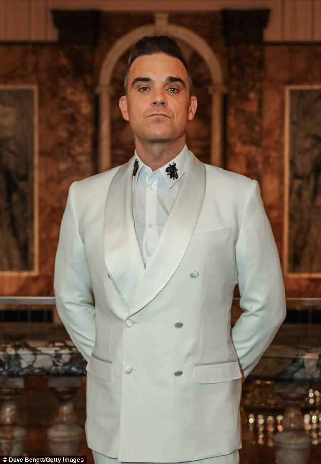 Rock star:Robbie Williams was a late comer at the bash as he shunned the red carpet and arrived looking dashing in an off-white suit with a jazzy shirt adorned with appliques at the collar