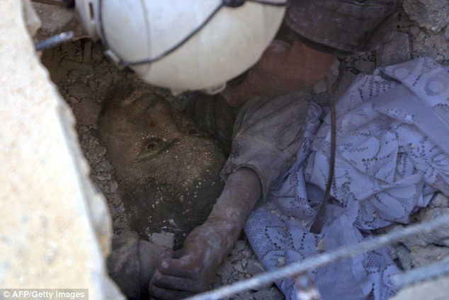 A young Syrian boy was rescued from the rubble by a member of the White Helmets following heavy air strikes on Aleppo
