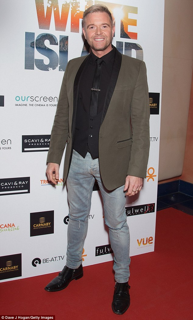 Trendy: Darren teamed faded ripped jeans with a tailored khaki suit jacket and black waistcoat
