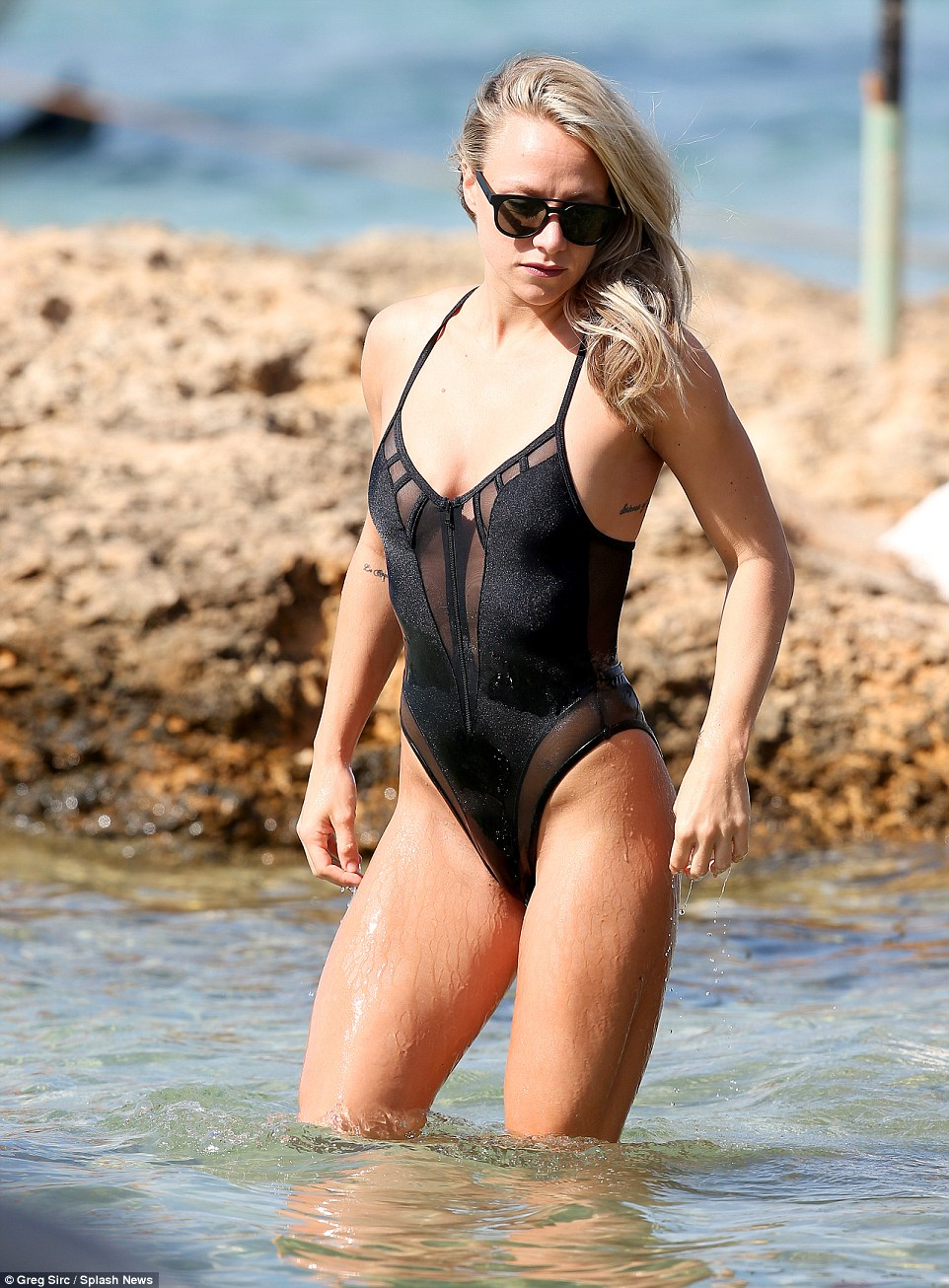 Beauty: The stunner cooled off with a plunge in the water, shielding her eyes from the sun with some funky shades