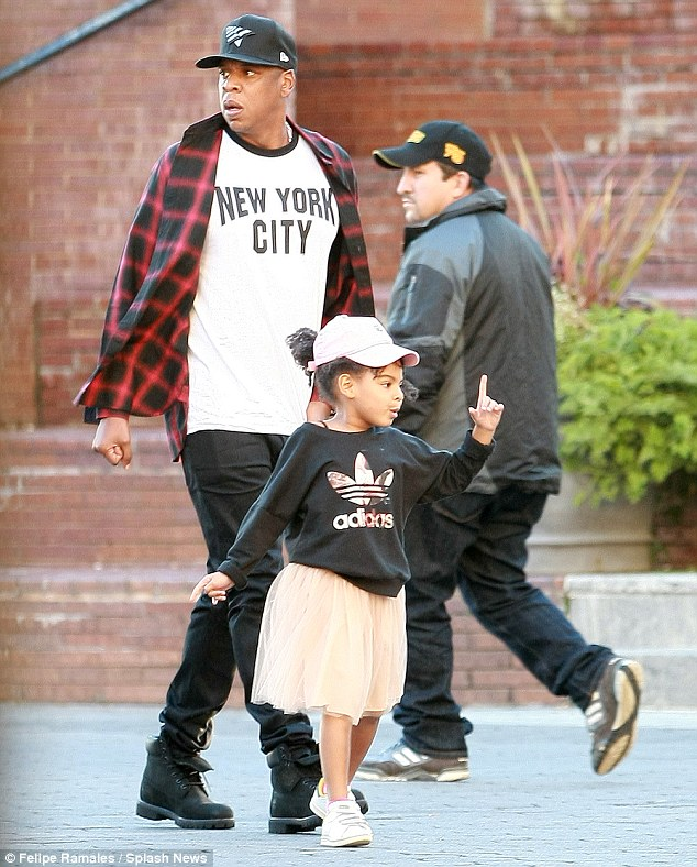 Daddy cool: Meanwhile Jay Z kept it casual in a plaid shirt, New York City T-shirt, black jeans and trainers