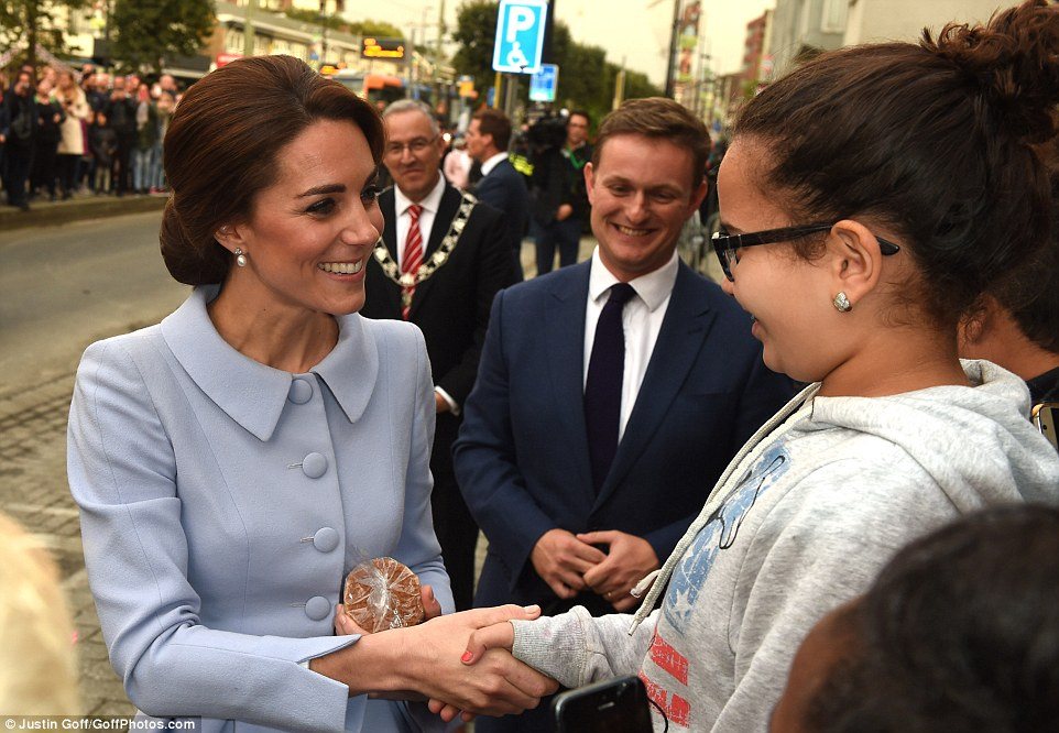 The Duchess looks delighted as she chats to local youngsters in Rotterdam and is handed an edible gift