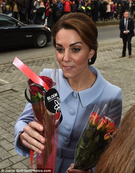 Kate is handed countless bouquets and bunches of roses