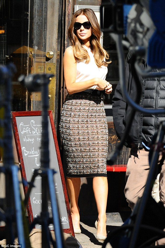 Camera ready: The 43-year-old star wore a pencil skirt and white blouse as she filmed at a cafe