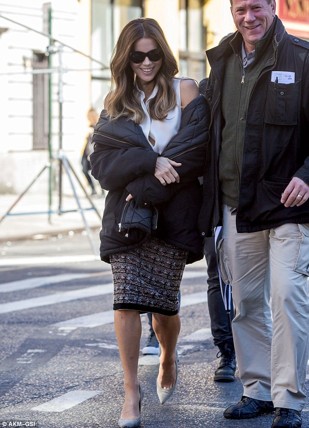 All smiles: The British-born star draped a winter coat around her shoulders as she was escorted across the set