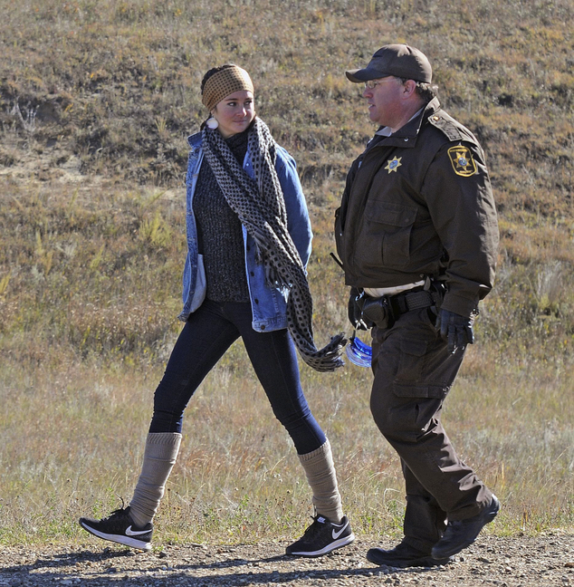 She is led to a transport vehicle by a Morton County Sheriff's deputy after being arrested