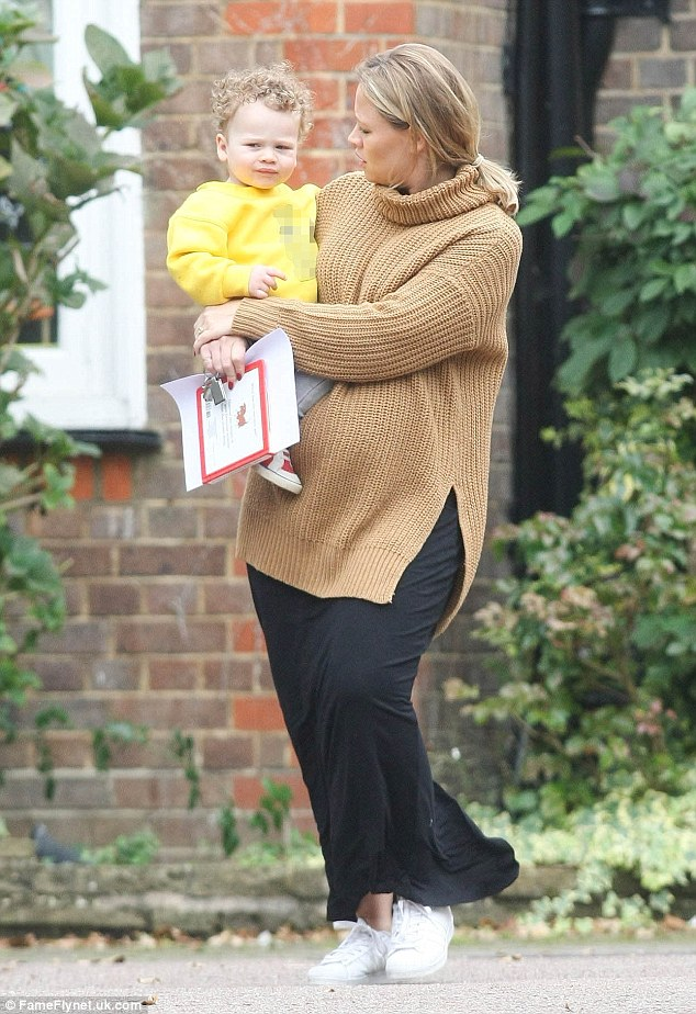 Comfy: The mum-of-one covered up her bump with a thick knit jumper