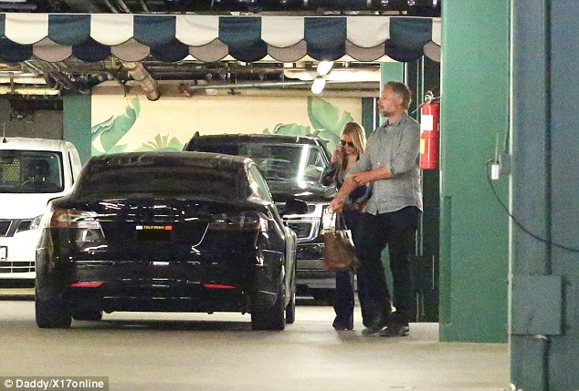 A hand on things: The chivalrous Johnson held his wife's bag as she chatted on the phone