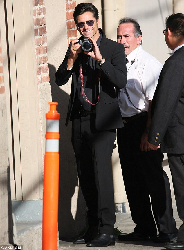Say cheese! John, who opted for a no tie look, hit the pavement in black dress shoes as he toted a camera in one hand