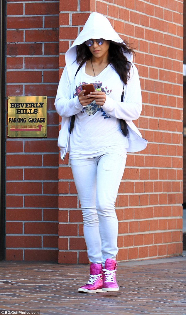 Casual: The actress attempted to go incognito with her hoodie and shades as she kept her fingers busy texting away