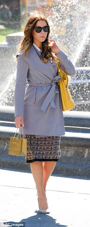 Stunning: She rocked a grey wrap-around belted coat which showcased her slim waist