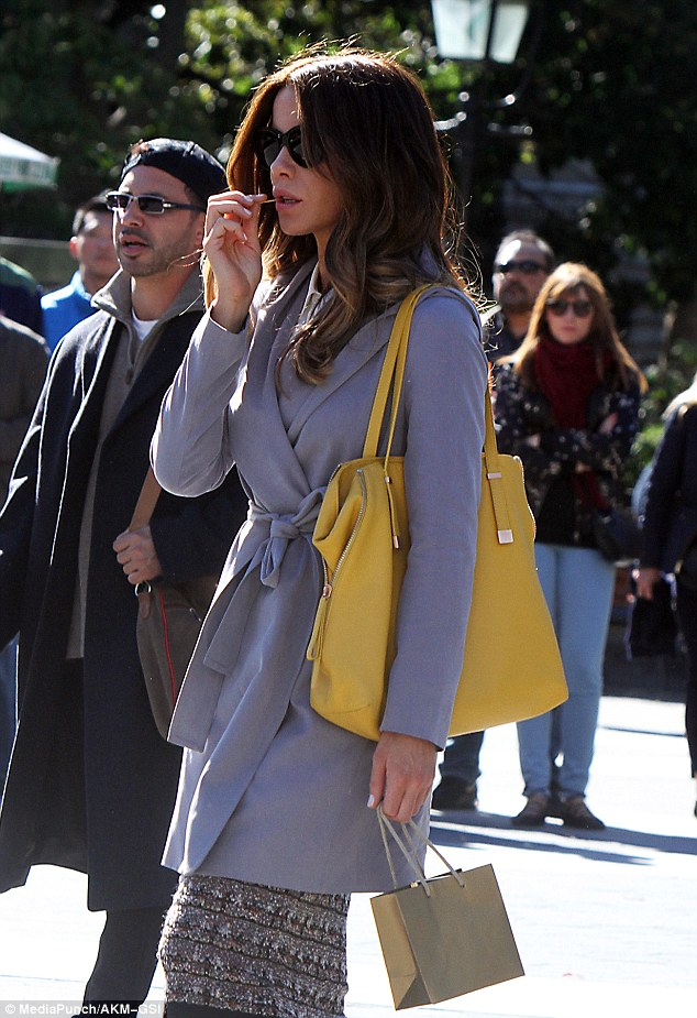 Filming: She colour clashed with a yellow tote bag on her hand