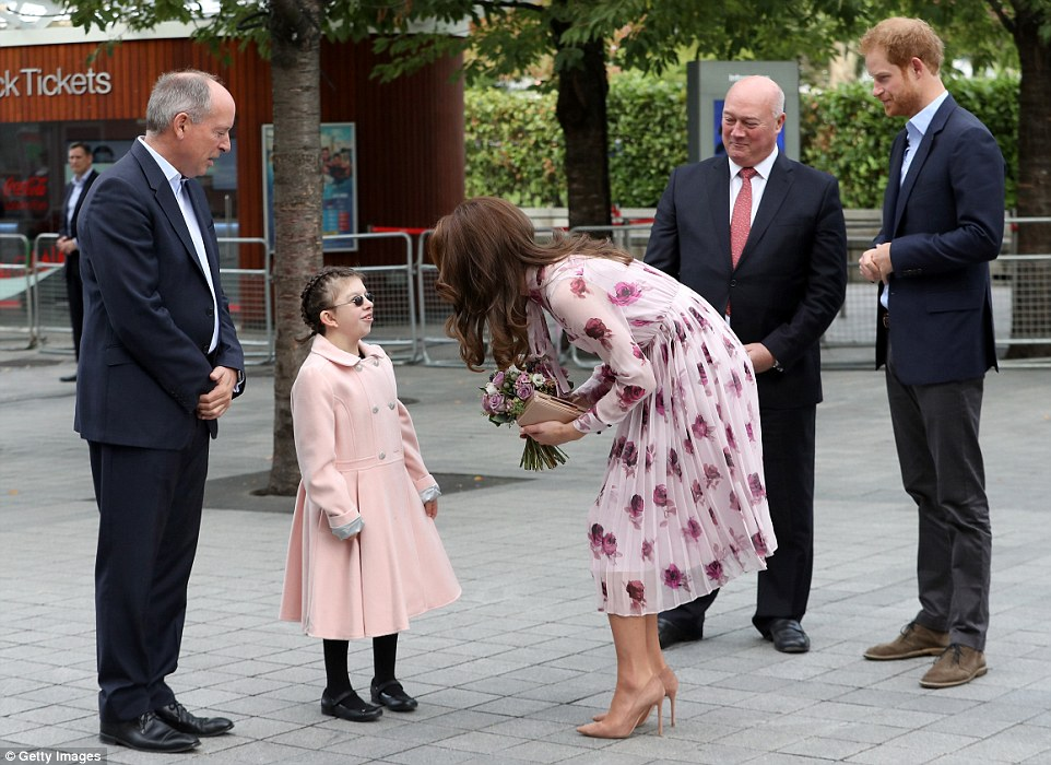 Kate receives a posy from Joanne Sibley, a student from Livability's Victoria Education Centre in Poole, Dorset, who was also dressed in pink for the special occasion