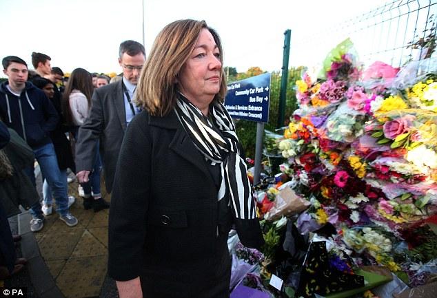 Cults Academy headteacher Anna Muirhead looks at tributes left outside the Aberdeen school