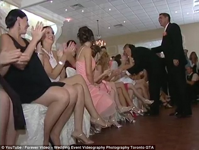 The groom, dressed in a dinner jacket, eventually reaches his wife and manages to identify her before pulling off his blindfold and leaning in for a kiss while guests cheer him on