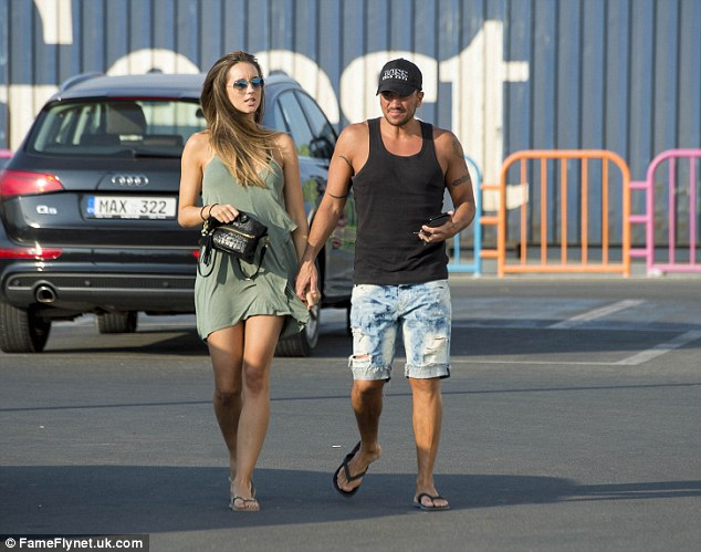 Blowing hot and cold: Despite the balmy Mediterranean heat, Emily clutched a jumper over her arm which contradicted her footwear choice of thin strap flip-flops