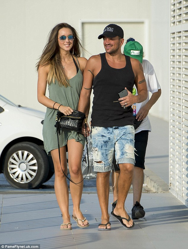 Happy couple: He ensured his muscular physique was fully on display as he wore a black baseball cap which matched his black flip flops