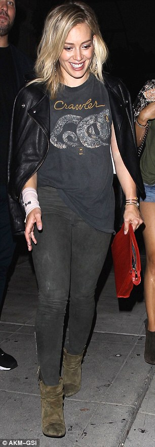 Rock chic: The actress who is also a successful music artist, wore a black graphic T-shirt, black skinny jeans and wrapped a black leather jacket around her shoulders