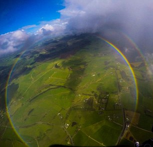 The optical phenomenon of the circular rainbow frames the landscape below. To see the full circle requires the observer to take an extreme vantage point, so the sunlight illuminating water particles will be both below and above them, lighting up a circle rather than the normal arc seen from ground level