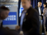 Hillary Clinton's campaign manager John Podesta, second from right, pauses while speaking with senior aide Huma Abedin aboard Clinton's campaign plane while ...
