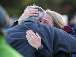 Mourners share a tearful embrace Monday, Oct. 10, 2016, during a vigil attended by about 1,000 at Harwood Union High School in Duxbury, Vt., held for the tee...