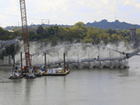 The steel arch of the Broadway Bridge falls into the Arkansas River after being pulled down by a pair of tug boats, Tuesday, Oct. 11, 2016 in Little Rock, Ar...