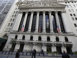 Pedestrians pass the New York Stock Exchange, Tuesday, Oct. 11, 2016, in New York. A batch of disappointing company earnings news helped put investors in a s...