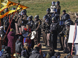 A person with a hand drum paces between law enforcement officers and a line of protesters along North Dakota Highway 6, south of St. Anthony, N.D., Monday, O...
