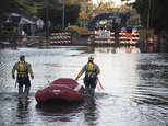 A swift water rescue team down a street covered by floodwaters caused by rain from Hurricane Matthew in Lumberton, N.C., Monday, Oct. 10, 2016. (AP Photo/Mik...