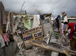A sign in French announcing a music concert sits among salvaged clothes drying on the remains of a home destroyed by Hurricane Matthew in Port-a-Piment, Hait...