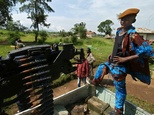 A child fighter stands by a machine gun fixed on a pickup at a military camp in Bunia, in northeastern DR Congo, in 2003