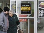 FILE - In this Tuesday, Nov. 25, 2014, file photo, a man and a woman leave an Hhgregg store in Mayfield Heights, Ohio. Consumer electronics chain Hhgregg Inc...