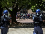South African policemen fire rubber bullets to disperse students from the University of Witwatersrand during clashes following a protest for free education o...