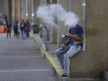 A Filipino uses an electronic cigarette outside a mall in Manila, Philippines Tuesday, Oct. 11, 2016. Health Secretary Paulyn Ubial said Tuesday she hopes Ph...