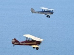 A Tiger Moth (R) and Travel Air 4000 biplane fly during a photocall for the launch of the Vintage Air Rally -- from Crete to Cape Town -- off the coast of Sh...