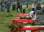 Myanmar border police prepare flag-draped coffins containing nine bodies of border guards killed in raids during a funeral ceremony at a cemetery in Maungdaw...