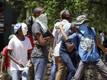 Protesting students throw stones at security officers, at the University of the Witwatersrand in Johannesburg, South Africa, Tuesday, Oct. 11, 2016. South Af...