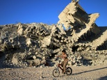 A boy rides a bicycle past a destroyed building in the rebel-held city of Daraa, in southwestern Syria, on September 27, 2016