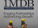 FILE - In this May 14, 2015 file photo, construction workers chat in front of a billboard for state investment fund 1 Malaysia Development Berhad (1MDB) at t...