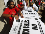 Retired Chicago school teacher Patricia Lofton counts through a stack of picket sign for Chicago Teachers Union members to pick up Monday, Oct. 10, 2016, in ...