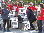 FILE - In this Sept. 11, 2012 file photo, Chicago public school teachers take a group picture as they walk a picket line outside a school in Chicago. Contrac...