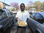 In this Friday, Sept. 30, 2016 photo, Kiziti Gezi, a street vendor, walks through cars as he sells neatly packed fruits to motorists in Harare, Zimbabwe. In ...
