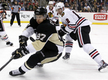 FILE - In this March 30, 2014, file photo, Pittsburgh Penguins' Sidney Crosby (87) works the puck in the corner against Chicago Blackhawks' Peter Regin (12) ...